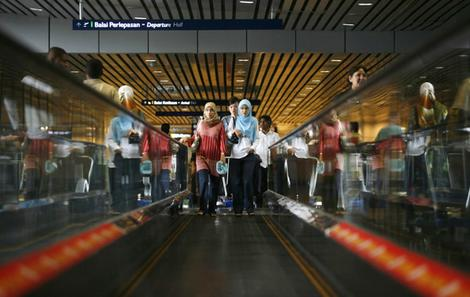 Women use the travelator at an airport in Sepang, outside Kuala Lumpur