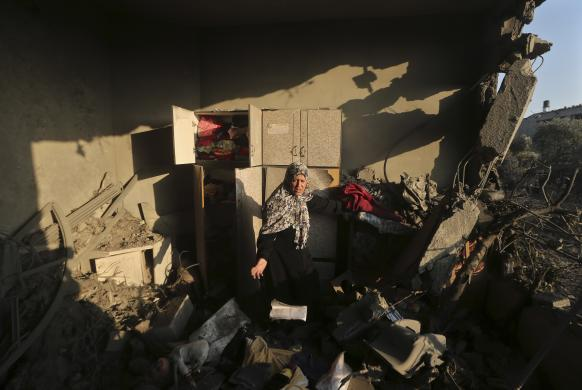 Palestinian woman inspects her house which police said was damaged in an Israeli air strike on a neighbouring house in Gaza City