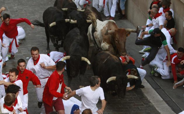 Runners sprint alongside Dolores Aguirre fighting bulls on Santo Domingo street, during the second running of the bulls of the San Fermin festival in Pamplona