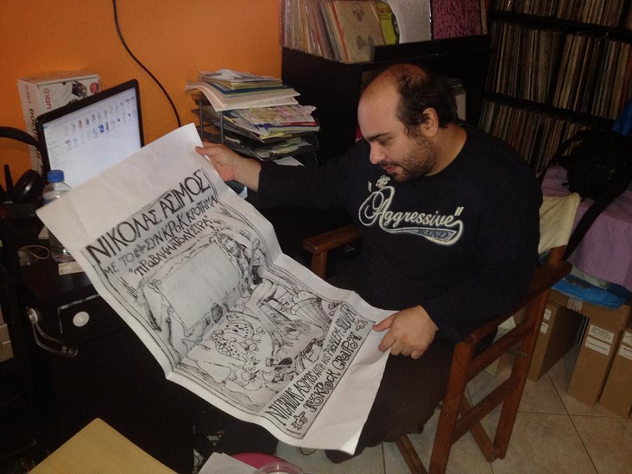 Ο Δ. Βασιλειάδης κρατά την αφίσα με το σκίτσο του Άσιμου, που δείχνει τον ίδιο να είναι ένα με την φύση.
