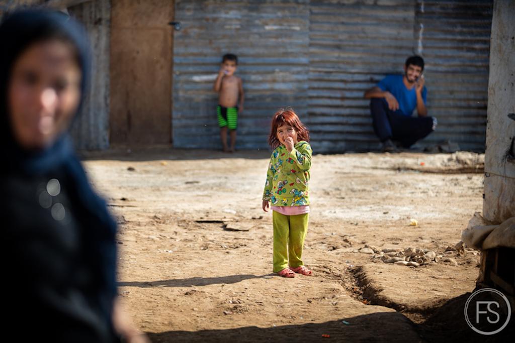 Ένα μικρό κορίτσι ανάμεσα στους συγγενείς της. Περίπου 20 οικογένειες ζουν σε αυτόν τον καταυλισμό.