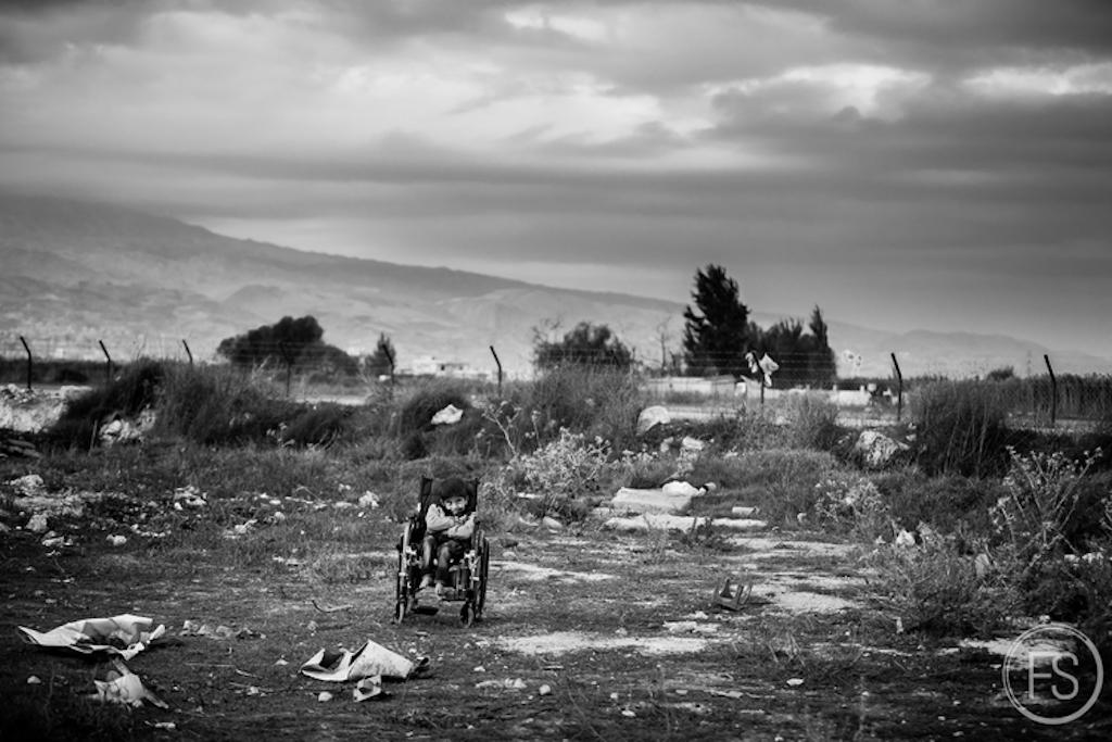 Ένα παιδί με ειδικές ανάγκες βρίσκεται μόνο του λίγο πιο πέρα από τον καταυλισμό.