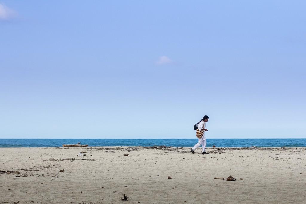 """Ένας ιθαγενής περπατάει κατά μήκος της θάλασσας με την κολομβιανή παραδοσιακή τσάντα """"mochila"""" κρεμασμένη στον ώμο."""