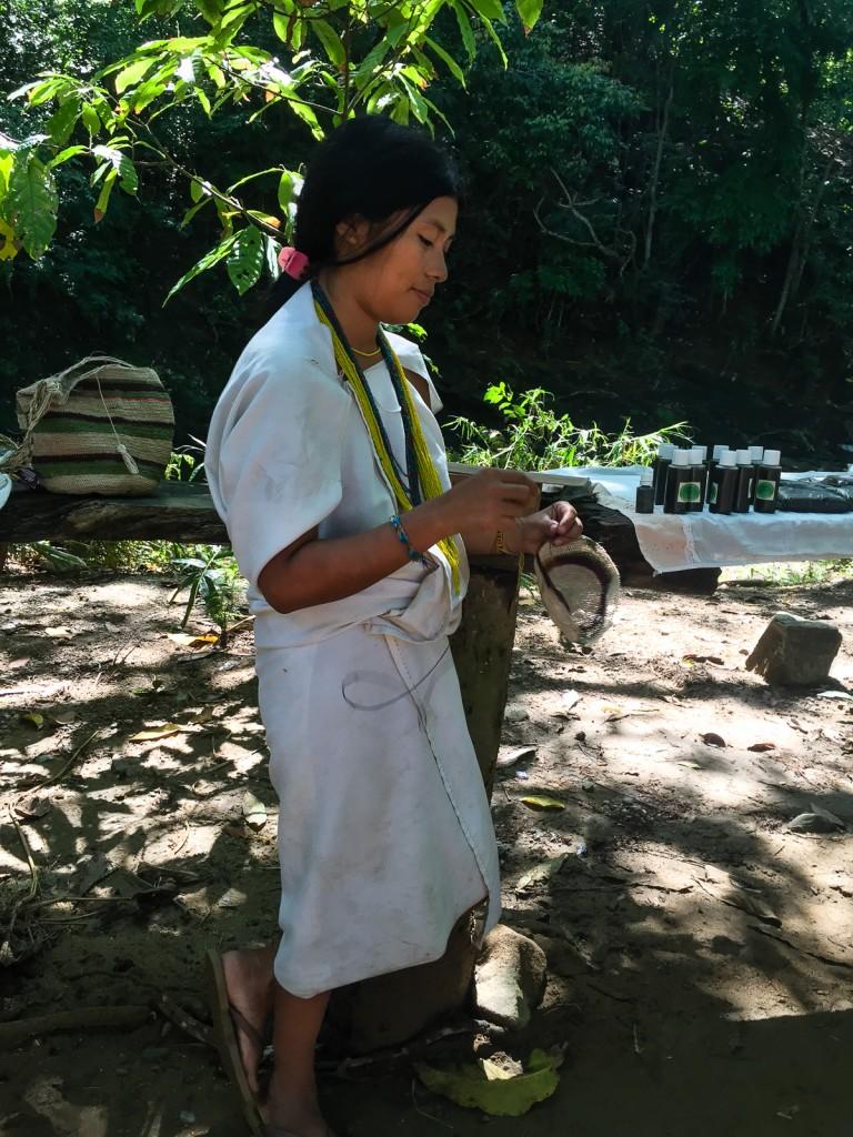 "Mία ιθαγενής μαμα-μικροπωλήτρια πλέκει την παραδοσιακή τσάντα ""mochila"". Ο πάγκος της μεταξύ άλλων είχε φύλλα κόκας και χειροποίητα γιατροσόφια με κάναβη και φύλλα κόκας."