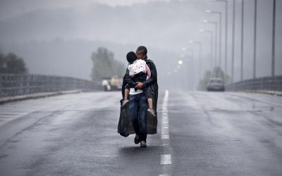 A Syrian refugee kisses his daughter as he walks through a rainstorm towards Greece's border with FYRO-Macedonia, near the Greek village of Idomeni, September 10, 2015. Thousands of refugees and migrants, including many families with young children, have been left soaked after spending the night sleeping in the open in torrential rain on the Greek- FYRO Macedonian border. REUTERS/Yannis Behrakis