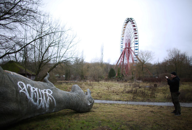 A man takes photograph of a fibreglass model of a dinosaur at the abandoned Plaenterwald amusement park in Berlin January 5, 2013. Berlin is littered with relics of its communist past, and one of the eeriest is the Spreepark, where the remains of what was once East Germany's only amusement park still stands. REUTERS/stringer (GERMANY - Tags: SOCIETY CITYSPACE) - RTR3C4IW